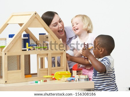 Pre-School Teacher And Pupils Playing With Wooden House - stock photo