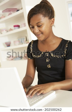 Pre-teen girl working on laptop at home - stock photo