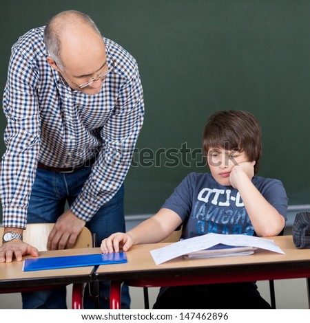 Preadolescent male student with hand on chin sitting at desk while teacher looking at him in classroom - stock photo