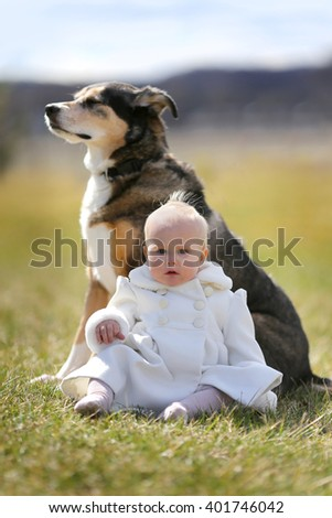 Precious One Year old Baby Girl Sitting Outside with Pet German Shepherd Dog. - stock photo