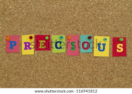 Precious word written on colorful sticky notes pinned on cork board.