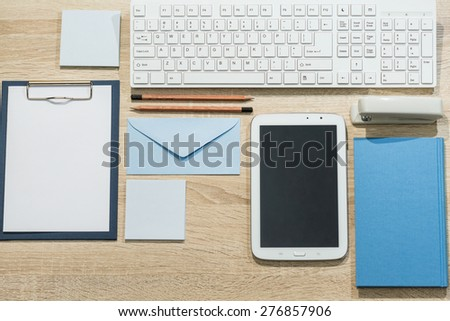 Precisely arranged wooden office desk with tablet and notebook - stock photo