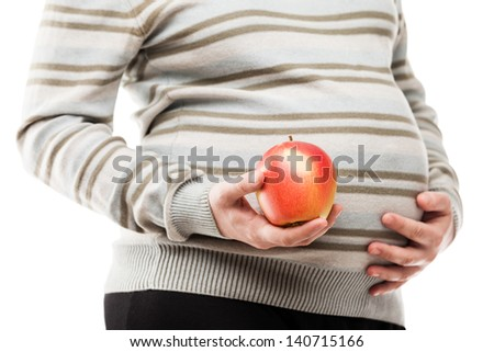 Pregnancy and new life concept - beauty pregnant woman hand holding red raw ripe apple fruit - stock photo