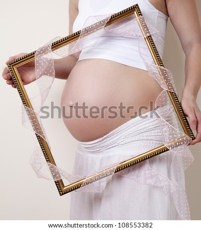 Pregnancy Concept - Pregnant Belly with a picture frame and pink ribbon - stock photo