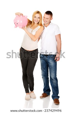 Pregnancy couple with piggy bank - stock photo