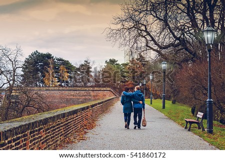 Pregnancy - happy pregnant couple walking in the park at the golden autumn time. couple is having fun in a city walk,Prague,Beautiful pregnant couple with big tummy is kissing,hugging