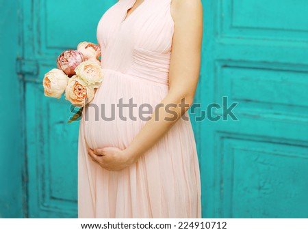 Pregnancy, motherhood and happy future mother concept - pregnant woman in dress with bouquet flowers against colorful wall - stock photo