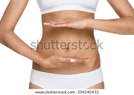 Pregnancy or diet concept, female hands protecting the stomach isolated on white background
