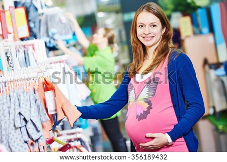 Pregnancy shopping. smiling pregnant woman choosing newborn clothes at baby shop store - stock photo