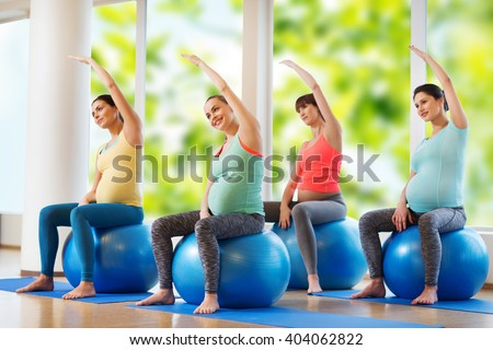 pregnancy, sport, fitness, people and healthy lifestyle concept - group of happy pregnant women exercising on ball in gym