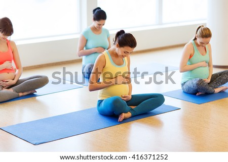pregnancy, sport, fitness, people and healthy lifestyle concept - group of happy pregnant women exercising yoga in lotus pose in gym - stock photo