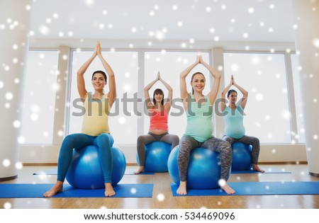 pregnancy, sport, fitness, people and healthy lifestyle concept - group of happy pregnant women exercising on stability balls in gym over snow