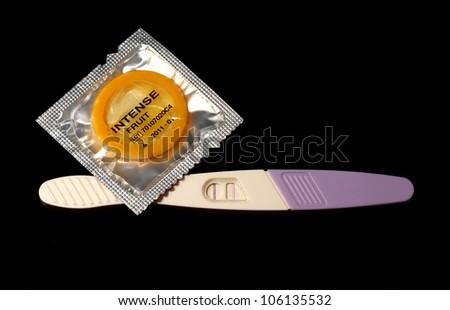 Pregnancy test and condom. - stock photo