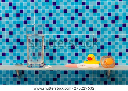 Pregnancy test, glass of water with pills on bath shelf on blue background - stock photo