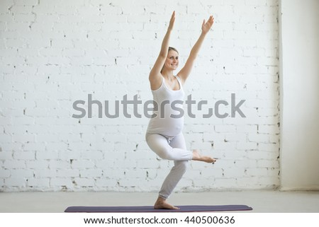 Pregnancy Yoga and Fitness concept. Portrait of beautiful young pregnant yoga model working out indoor. Pregnant happy fitness person enjoying yoga practice at home. Prenatal Chair Pose, Utkatasana - stock photo