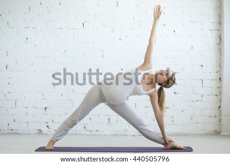 Pregnancy Yoga and Fitness concept. Portrait of beautiful young pregnant yoga model working out indoor. Pregnant happy fitness person practicing yoga at home. Prenatal Utthita Trikonasana pose - stock photo