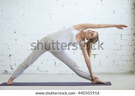 Pregnancy Yoga and Fitness concept. Portrait of beautiful young pregnant yoga model working out indoor. Pregnant happy fitness person enjoying yoga practice at home. Prenatal Extended Triangle pose - stock photo