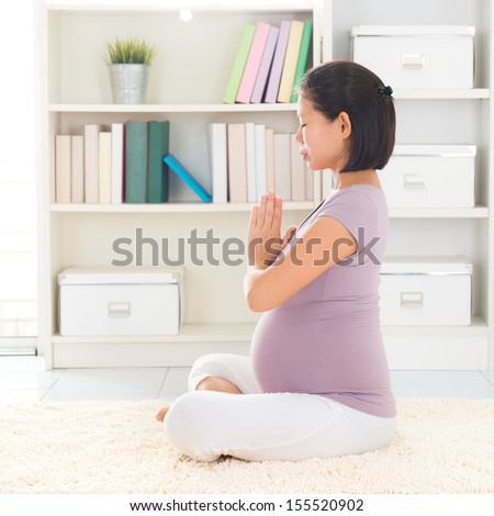 Pregnancy yoga meditation. Full length healthy 8 months pregnant calm Asian woman meditating or doing yoga exercise at home. Relaxation yoga lotus prayer pose. - stock photo