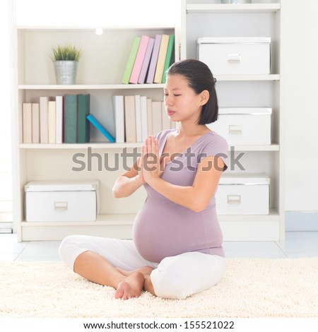 Pregnancy yoga meditation. Full length healthy 8 months pregnant calm Asian woman meditating or doing yoga exercise at home. Relaxation yoga positions. - stock photo