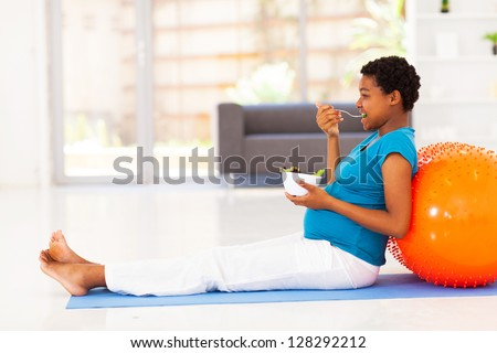 pregnant african american woman eating healthy salad on exercise mat - stock photo