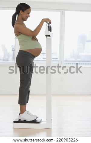 Pregnant African woman on scale - stock photo
