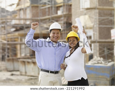 Pregnant Asian couple cheering at construction site