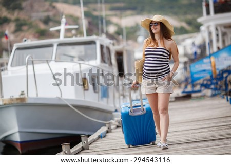 Pregnant beautiful woman by the sea with summer straw hat? sunglasses and suitcase. Vacation concept - stock photo
