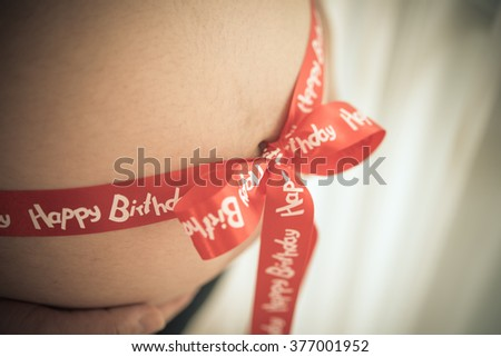 pregnant belly decorated with ribbon as a present,vintage - stock photo