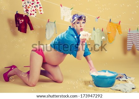 Pregnant blonde pin up woman doing laundry with soap bubbles - stock photo