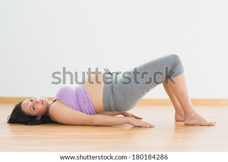 Pregnant brunette lying on floor in bridge pose in a fitness studio