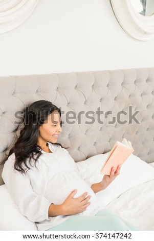 Pregnant brunette reading a book on the bed
