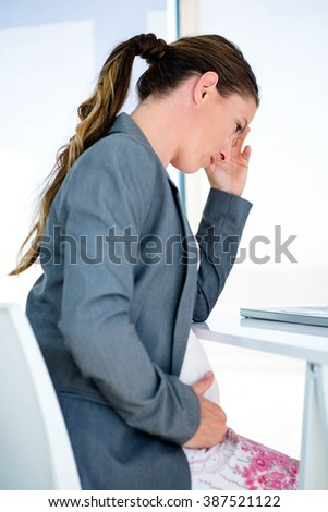 pregnant business woman sitting at her desk with her head in her hands - stock photo