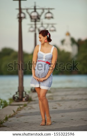 Pregnant caucasian woman takes rest outdoor
