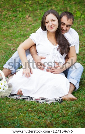 Pregnant couple are sitting on the grass in the park - stock photo