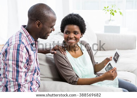 Pregnant couple sitting on sofa and looking at ultrasound scan at home - stock photo