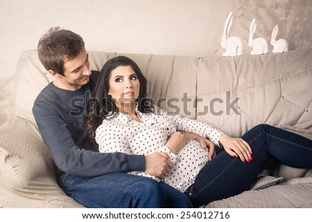Pregnant couple sitting on the sofa at home  - stock photo