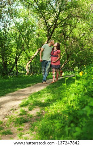 Pregnant couple walking at the park kissing and holding hands. Full lenght - stock photo