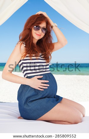 Pregnant fashion woman relaxing on the beach - stock photo