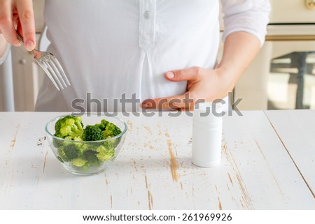 Pregnant female choosing between broccoli and vitamins, kitchen background - stock photo