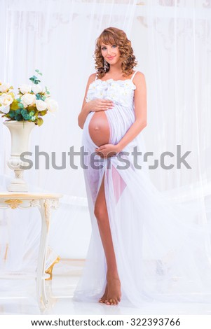 Pregnant girl in a white dress with orchids as a goddess