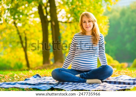 Pregnant girl in jeans and a striped sweater resting in a park - stock photo