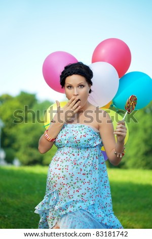 Pregnant girl with balloons in the park - stock photo