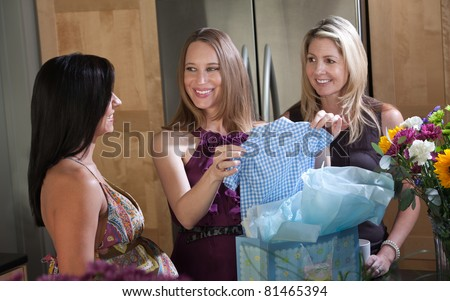 Pregnant lady holds blue baby clothes with friends in kitchen - stock photo