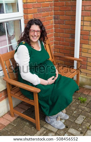 Pregnant lady with glasses wearing a green maternity dress and holding her pregnant belly with a big smile sitting in front of her house on a wooden bench