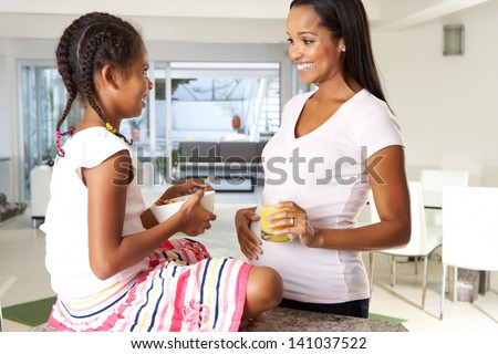 Pregnant Mother And Daughter Drinking Juice In Kitchen - stock photo