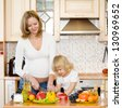 pregnant mother and daughter in kitchen - stock photo