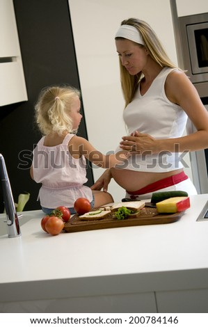 Pregnant mother and daughter in the kitchen eating - stock photo