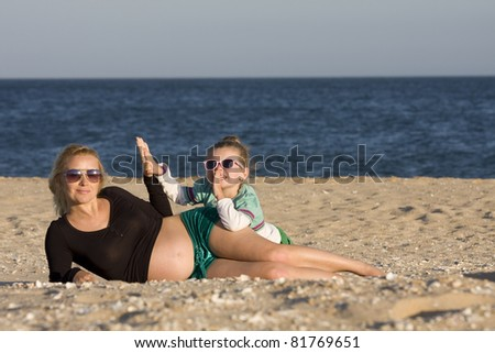 Pregnant mother and daughter lying on the beach with sunglasses - stock photo