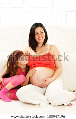Pregnant mother and daughter sitting together - stock photo