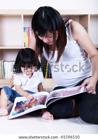 Pregnant mother and her daughter reading together. - stock photo